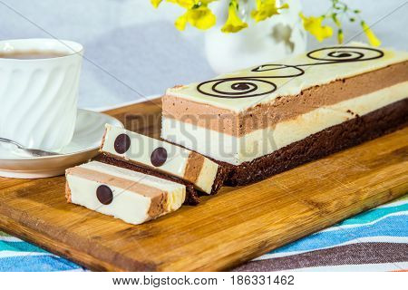 Three-layer chocolate cake, decorated with chocolate patterns. Background - white vase with flowers and porcelain cup with hot tea.  Holiday cake Three-colate. Professional bakery