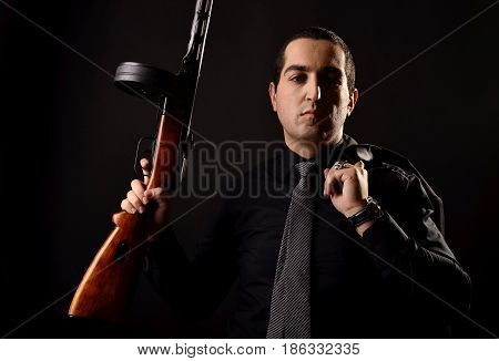 Handsome Young Man In Black Suit With Machine Gun In His Hands On On A Black Background