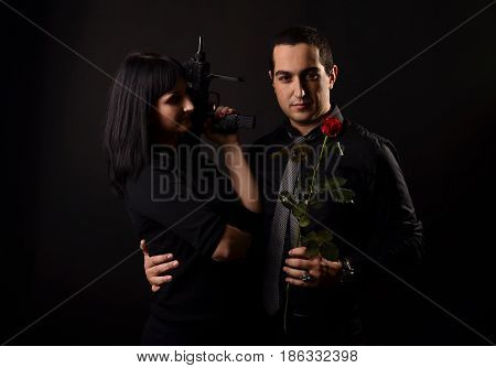 Man In Black Shirt With Red Rose In Hand Huds The Girl With Gun While She Looking At Him. Love Story