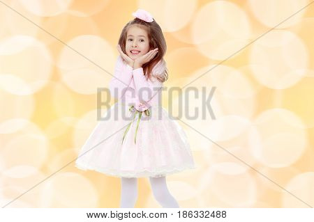 Dressy little girl long blonde hair, beautiful pink dress and a rose in her hair.She holds the palm of your hand near their cheeks.Brown festive, Christmas background with white snowflakes, circles.