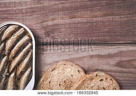 Tin can of sprats, sardines with bread pieces on wooden table. Top view and free space.