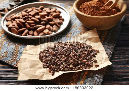 Plate with aromatic cocoa beans, powder and nibs on wooden table