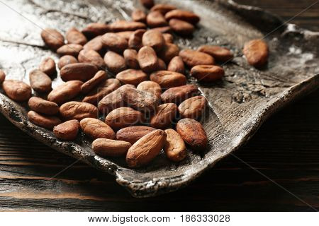 Tray with aromatic cocoa beans on wooden table