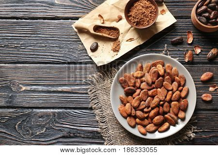 Plate with aromatic cocoa beans on wooden table