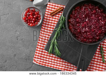 Delicious cranberry sauce in pan on kitchen table