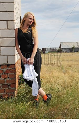 The young woman lean on house brick wall.