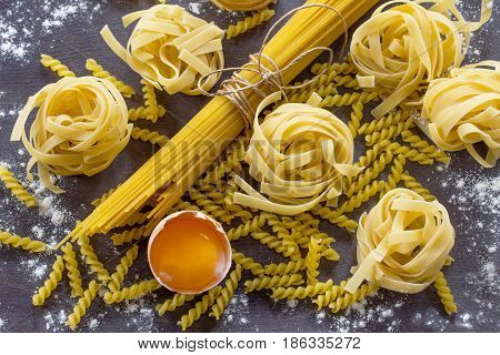 Different Kinds Of Pasta Spaghetti, Fusilli, Fettuccine And Raw Egg Yolk On The Kitchen Wooden Table