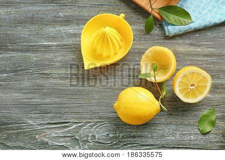 Manual juicer with fresh lemons on wooden background