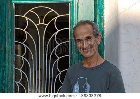 Amorgos Island Greece - October 2015: Greek man is posing infront of his distillery factory