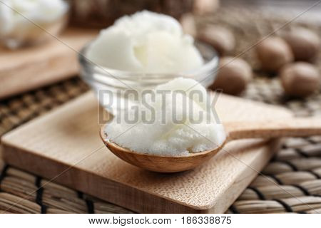 Shea butter in spoon and bowl on board, close up