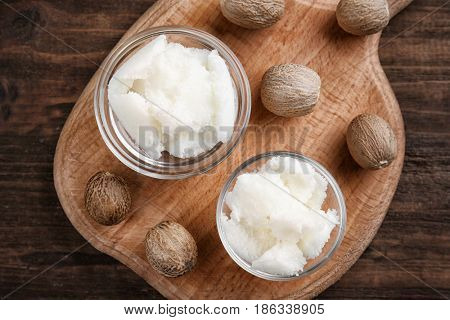 Shea butter in bowls on wooden background, top view
