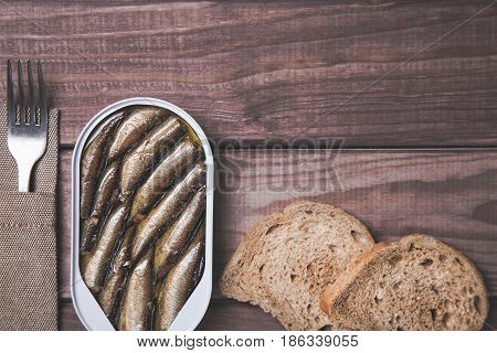 Tin can of sprats, sardines with bread pieces and fork on wooden table. Top view and free space.