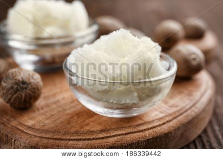 Shea butter in bowls on wooden background, close up
