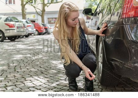 Desperate Woman Checking The Damage To Her Car