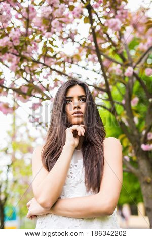 Portrait Of Beautiful Young Woman Enjoying Sunny Day In Park During Cherry Blossom Season On A Nice