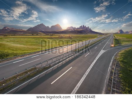 Open highway to the mountain range towards the rising sun. Straight motorway in beautiful desert landscape.