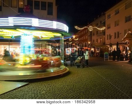 Friedrichshafen Germany - November 28 2015: funfair and huts for the Christmas market with floodlights