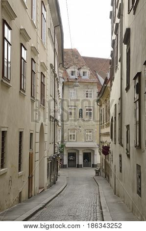 GRAZ, AUSTRIA - MARCH 19, 2017: Narrow street in beige colors in the old city of Graz the capital of federal state of Styria Austria.