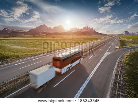 Lone bus with trailer driving towards the mountain range at beautiful sunset. Fast blurred motion drive on the straight freeway in beautiful landscape. Travel concept.