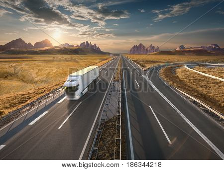 Lone delivery truck driving from the mountain range towards the setting sun. Fast motion drive on the straight freeway in beautiful landscape. Transportation concept.