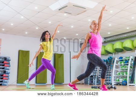 Smiling women enjoying group Zumba dance classes in studio. Two female athletes doing aerobics indoors in gym.