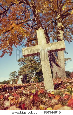 Cross in autumn cemetery. Vintage filter effects.