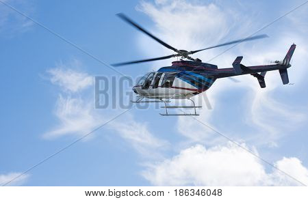 Helicopter Flying Through A Blue Sky With Clouds