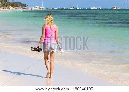 Young woman walking on perfect tropical beach and turquoise ocean water Romantic seashore blue sea and coco palm trees