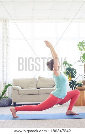 Elegant lady practicing blaster pose with hands up