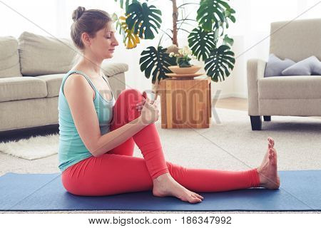 Side view of gorgeous female meditating and starching muscles on yoga mat