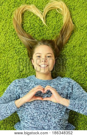 Pretty teen girl lies on the carpet