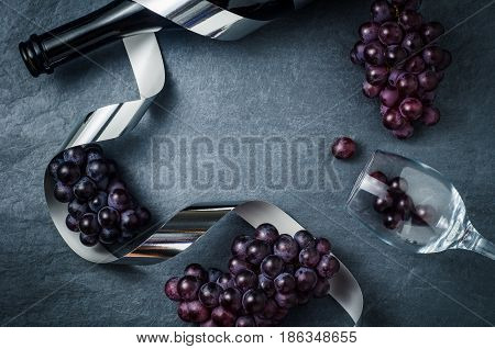 Wineglass bottle with ripe grapes and ribbon on black stone background.