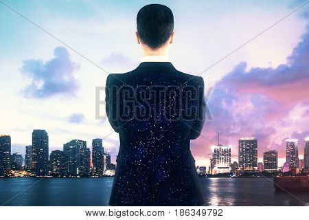 Back view of young businessman with space suit looking at city with. Creativity concept