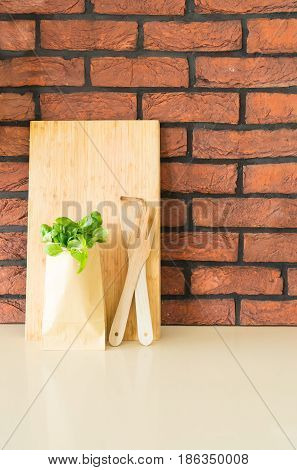 kitchen table top detil with wooden cutting board, cutlery and green herb