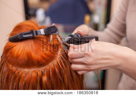 The Hairdresser Does Hair Extensions To A Young, Red-haired Girl, In A Beauty Salon. Professional Ha