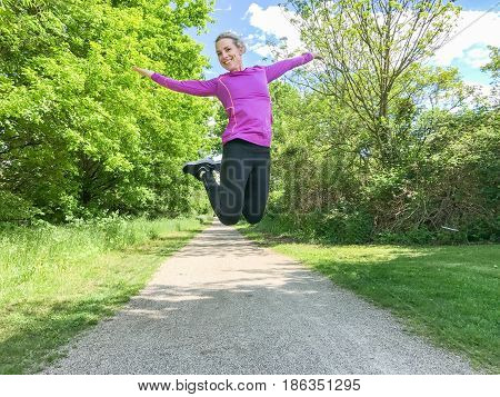 Joyful young woman leaping in the air with her arms extended as she celebrates the sunny spring weather outdoors in a wooded park