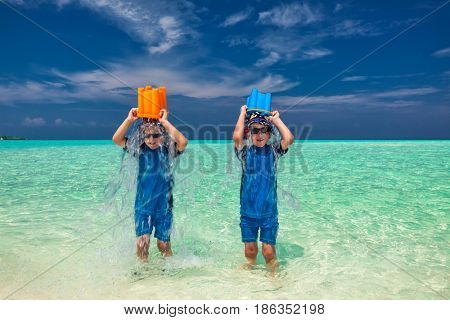 Twin brothers on tropical holidays having fun pouring water over their heads