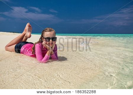 Young smiling girl with sunglasses laying on tropical beach, Maldives