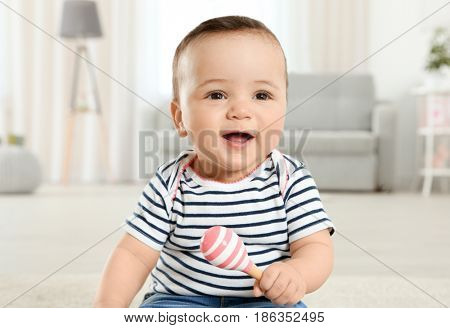 Cute little baby with rattle at home