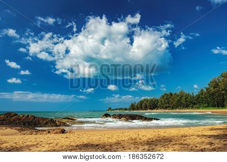 Beautiful seascape with sea and rock in Nang Thong Beach, Khao Lak, Thailand. View of bright blue sea with protruding stones and vacationers. Nature composition.