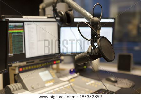 Microphone in front of the sound mixer and computers in broadcasting radio studio. New radio station studio.