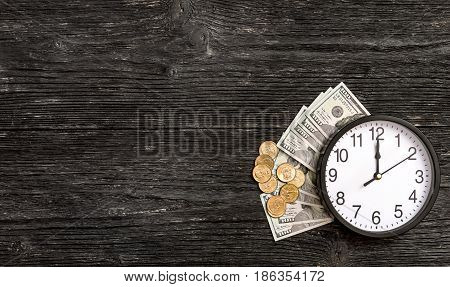Clock with money on black wooden background. Time is money.