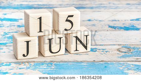June 15th. Wooden cubes with date of 15 June on old blue wooden background.