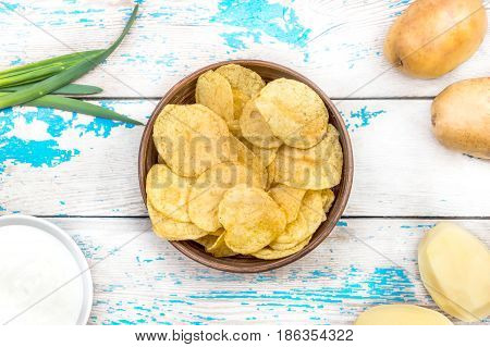 Bowl with potato chips and ingredients for chips - raw potato green onion and sour cream on the table.