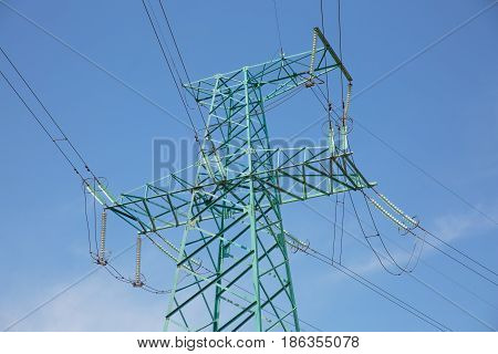 High voltage pylon close to motorway. Power transmission line