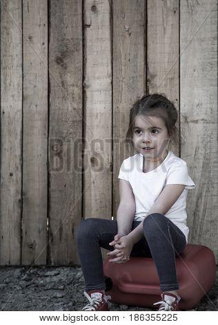 Little Girl Sitting On Wooden Background