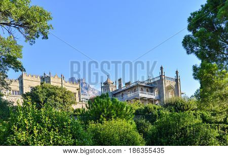 Vintage old-fashioned castle with turret, sunny morning. Vorontsov palace, Alupka, Crimea. Blue sky, mountain landscape. Scottish Baronial, Mughal architecture, Gothic Revival architecture styles.