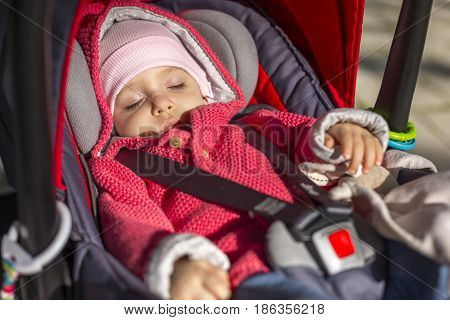 Beautiful 1 year old baby is sleeping in a car seat attached in a stroller. Outdoors in cold weather