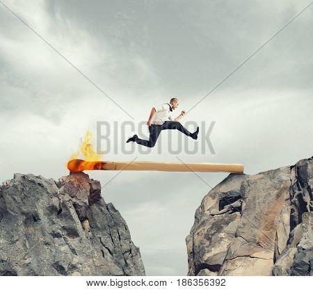 Businessman runs over a match lit between two mountains