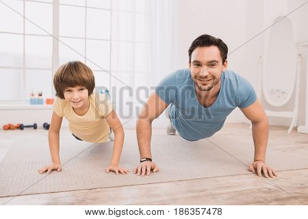 Father and son exercise together at home healthy active lifestyle
